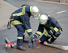 german fire fighters feuerwehr plugging in fire hose and mobile hydrant